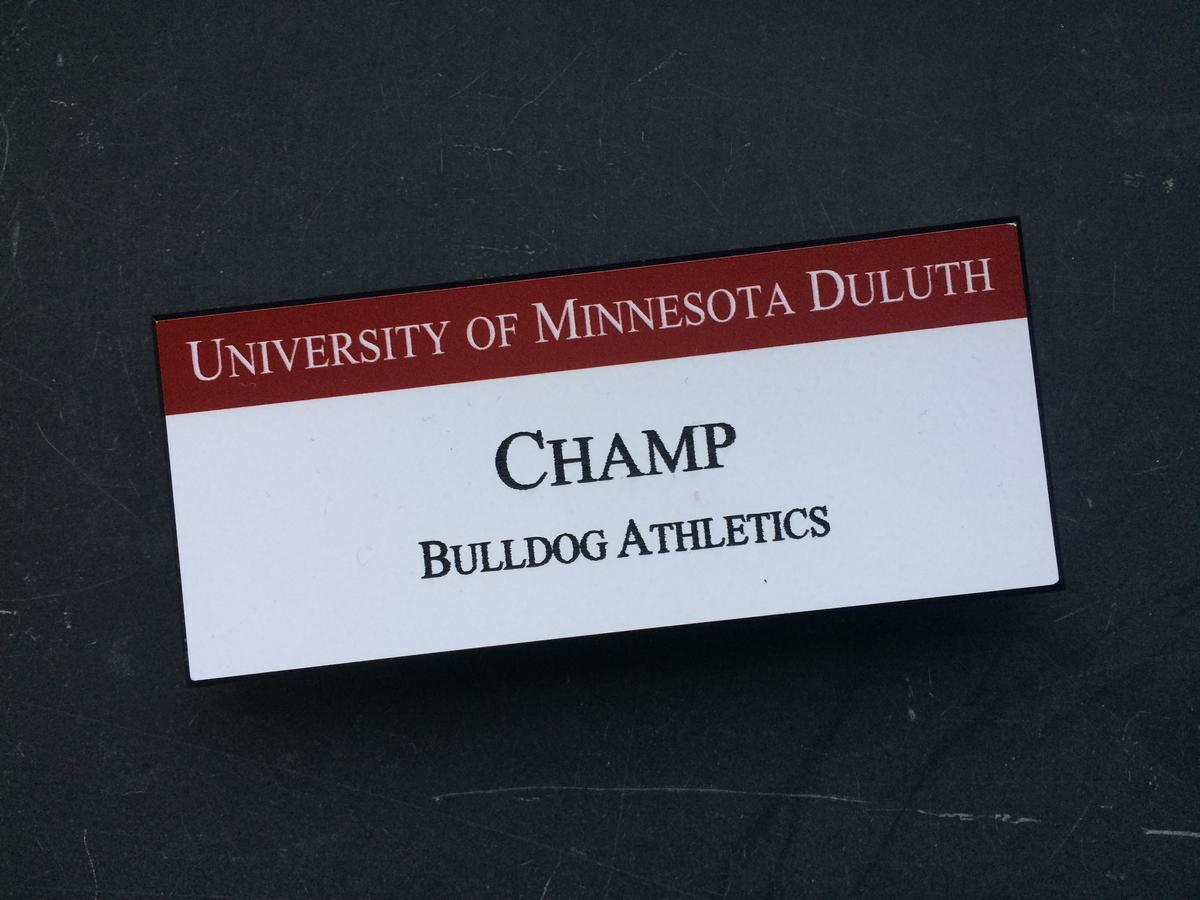 "A white name tag with text reading ""University of Minnesota Duluth, Champ, Bulldog Athletics."""